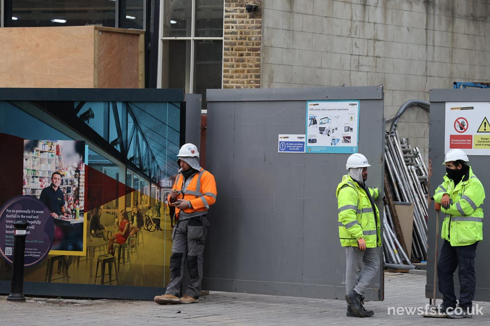 Builders in front of The Works construction site